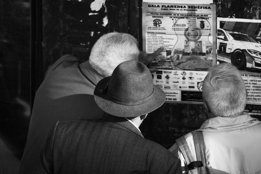 Tres hombres mirando un cartel