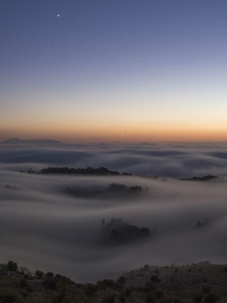 Tres planetas sobre mar de nubes